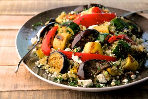 Mediterranean Quinoa and Grilled Vegetable Salad on platter with gray border on rough wood table