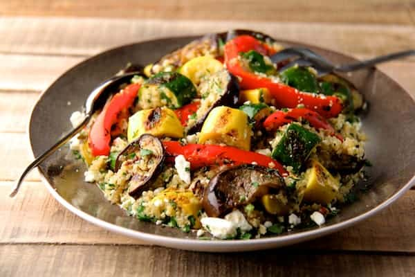 Photo of quinoa and vegetable salad with feta cheese on gray-rimmed platter on rough wood surface.