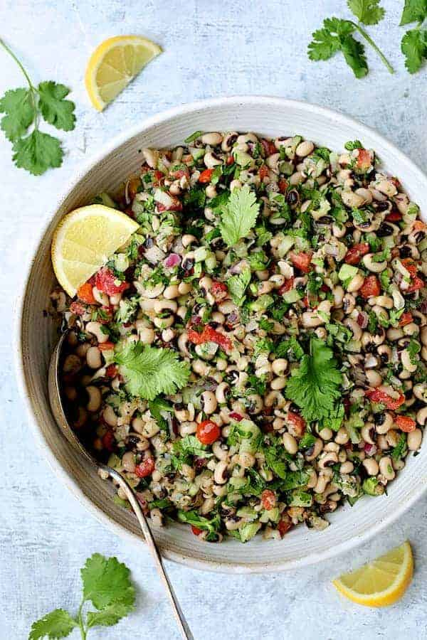 Photo of Spicy Black-Eyed Pea Salad in white bowl garnished with cilantro and lemon wedges.