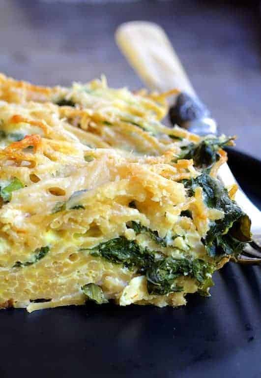Photo of one piece of baked spaghetti frittata with fork on black plate.
