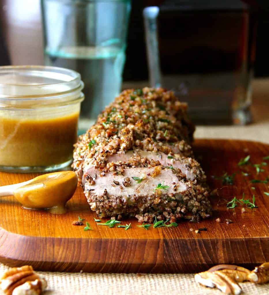 Pecan-Crusted Pork Tenderloin with Bourbon - Mustard Sauce on wood cutting board sliced