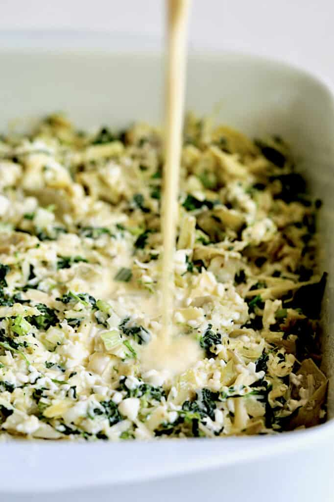 Custard combination being poured over spinach artichoke combination