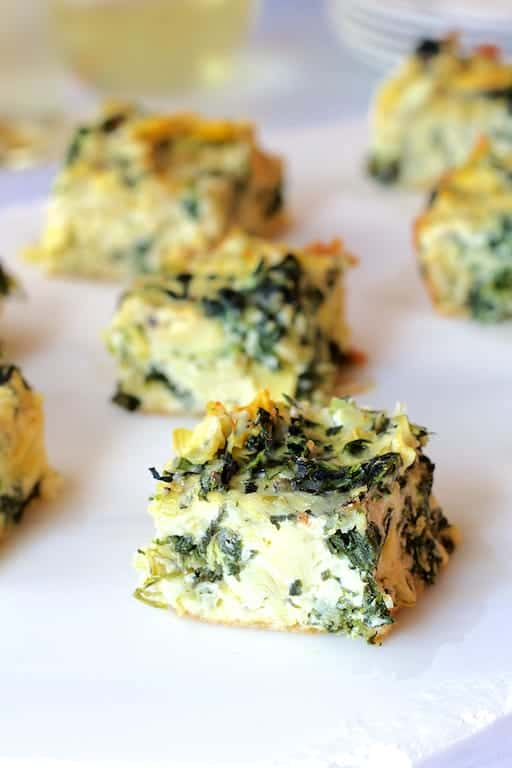 Spinach Artichoke Squares - Straight-on shot of squares on white serving platter