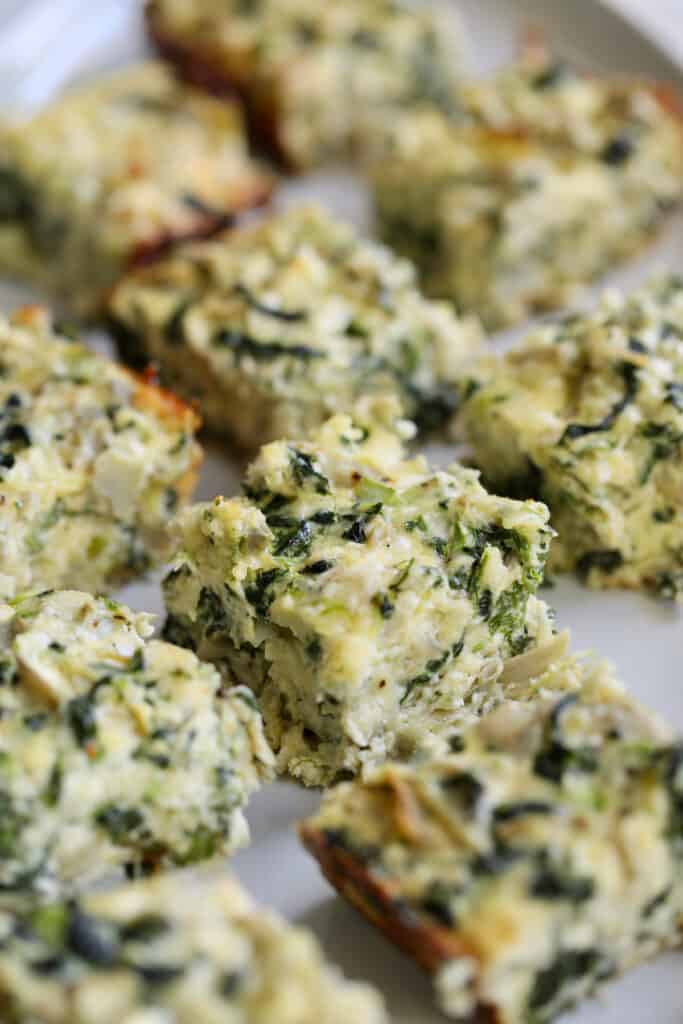 Spinach Artichoke Squares - Straight-on close-up shot of squares on white platter