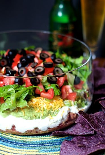 Healthier 7-Layer Dip - Hero shot of dip in tall glass bowl with blue corn chips and beer in the background