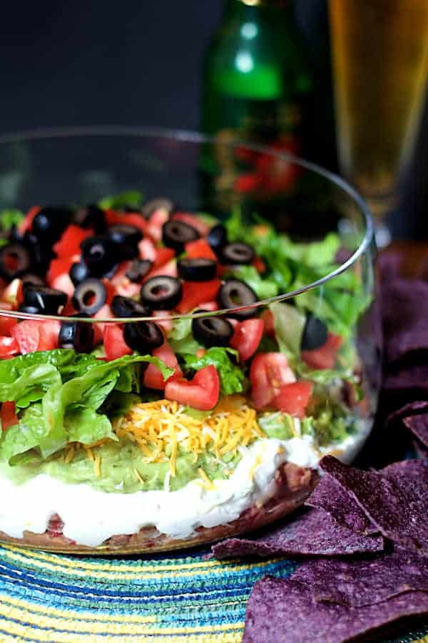Photo of Healthier 7-Layer Dip in tall glass bowl with blue corn chips and beer in the background.