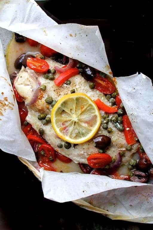 Photo of Mediterranean Fish en Papillote in parchment paper on black background.