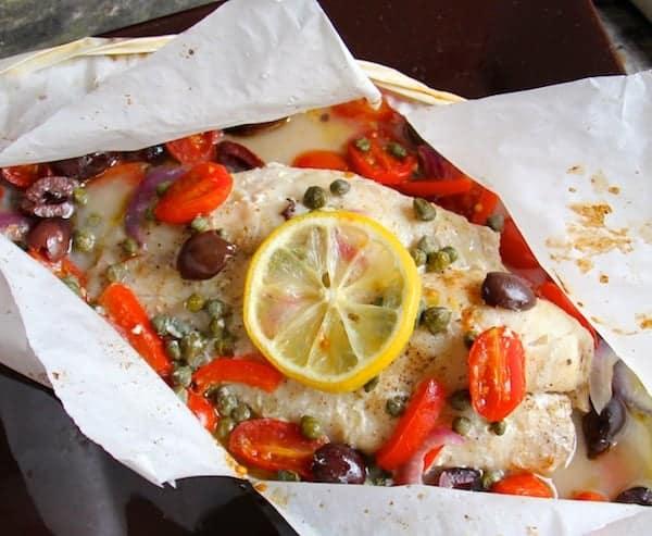 Close-up photo of Mediterranean Fish en Papillote garnished with lemon.
