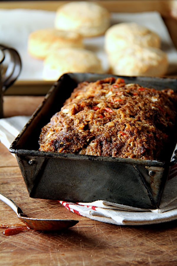 Photo of Chili Glazed Meatloaf without the glaze on top in aged loaf pan with biscuits in the background.