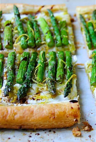 Asparagus, Spring Onion and Fontina Tart - Straight-on hero shot of tart garnished with lemon zest and balsamic vinegar