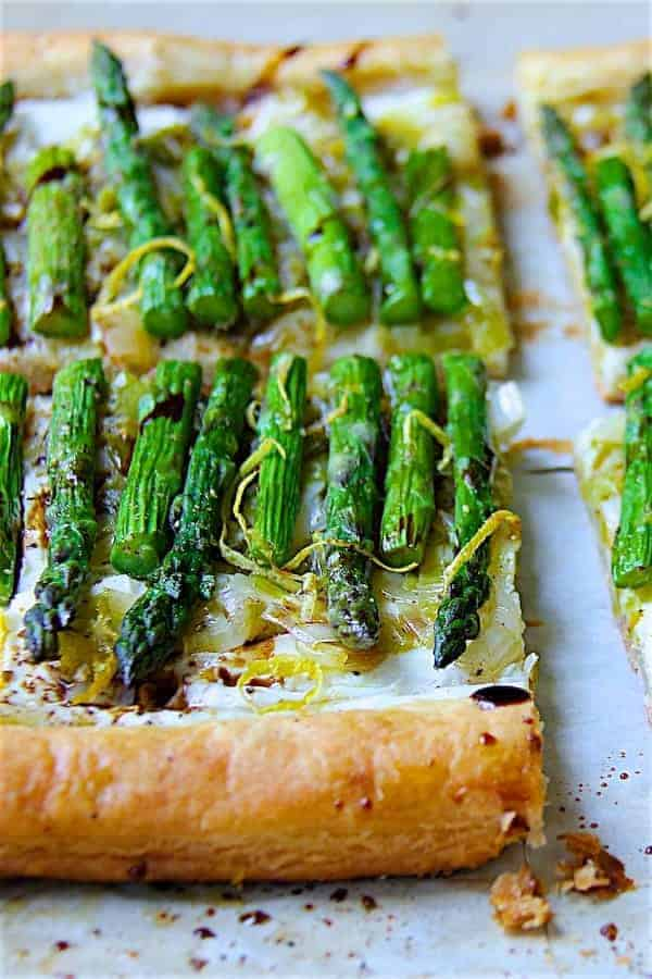 Asparagus, Spring Onion and Fontina Tart - Straight-on hero shot of tart garnished with lemon zest and balsamic vinegar