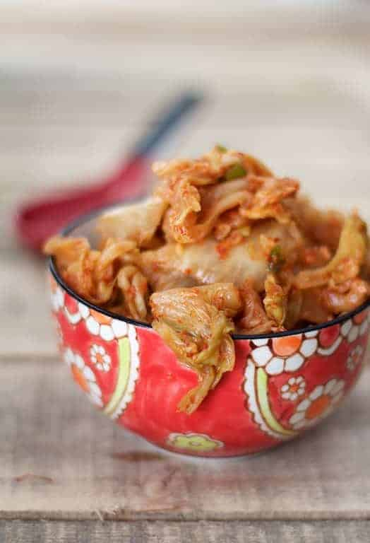 Easy Homemade Kimchi in red Asian-style bowl on wood background