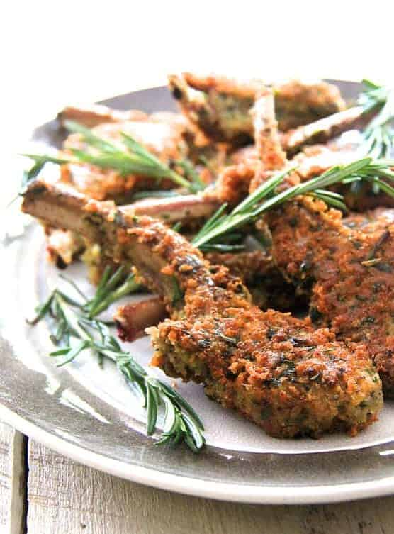 Parmesan and Herb Crusted Lamb Chops - Close-up shot of lamb chop on gray-rimmed platter garnished with rosemary