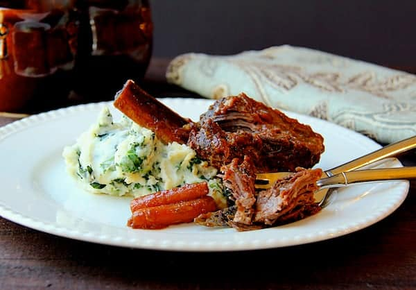 Stout-Braised Beef Short Ribs and Colcannon - On white plate with carrots and fork shredding the meat