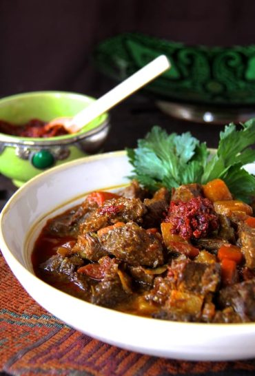 Moroccan Beef Stew in white bowl with harissa, garnished with celery leaves