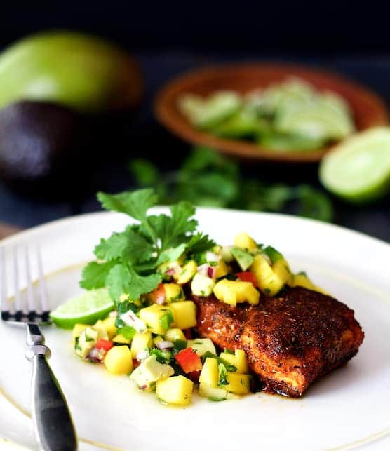 Blackened Halibut with Mango and Avocado Salsa - Hero shot of dish on white plate garnished with cilantro sprigs and lime wedges