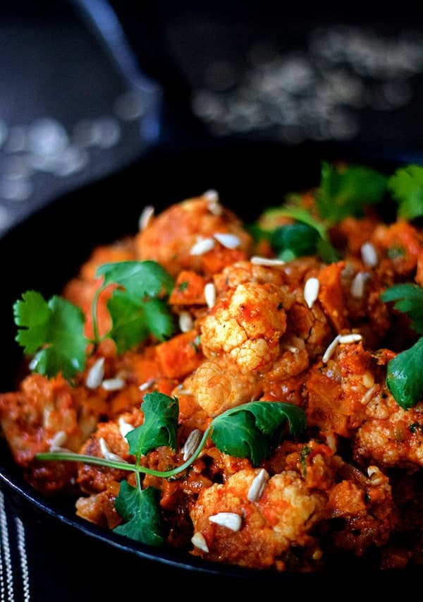 Photo of Cauliflower and Sweet Potatoes in Roasted Red Pepper Mole in cast iron skillet garnished with cilantro and sunflower seeds.