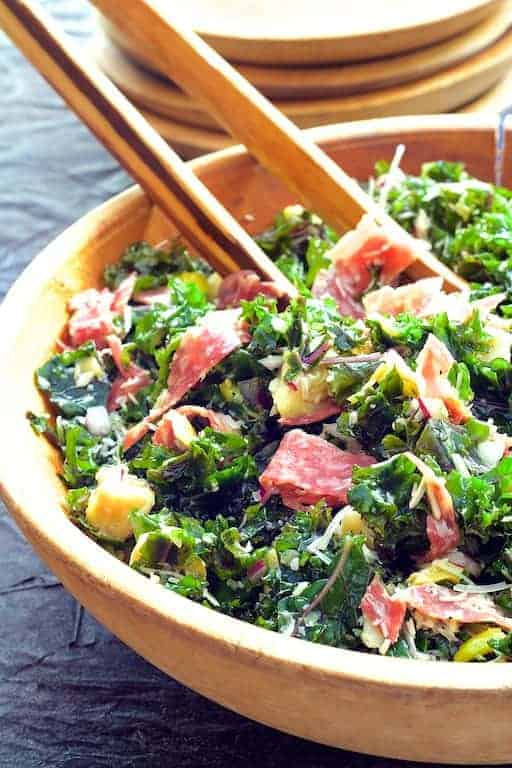 Massaged Kale Antipasto Salad - Salad in wood salad bowl being tossed with tongs