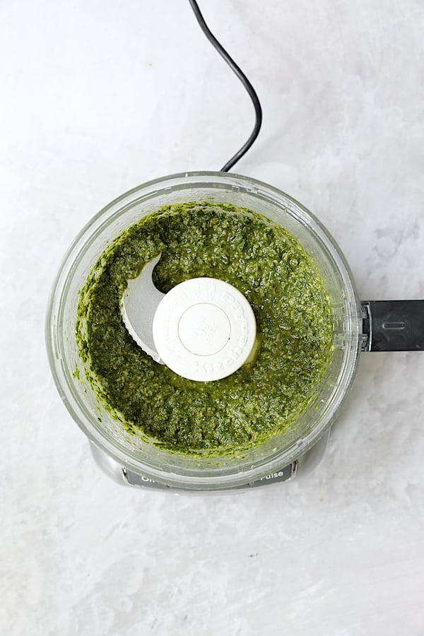 Overhead shot of finished basil pesto in food processor