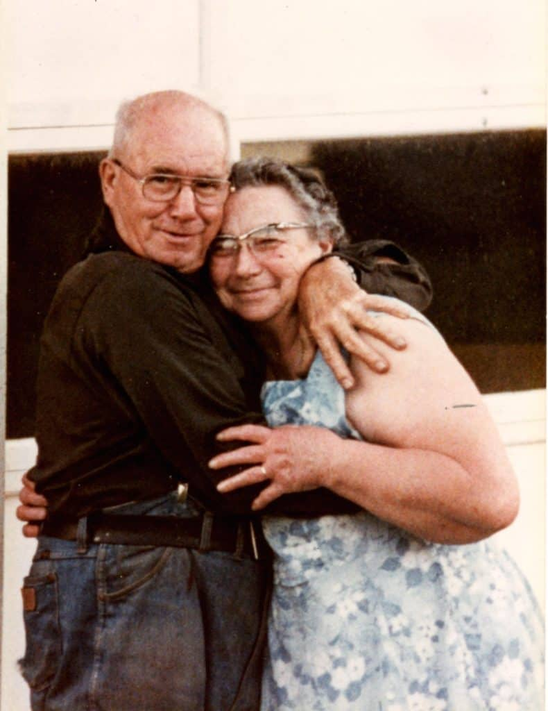 Photo of an elderly couple embracing.