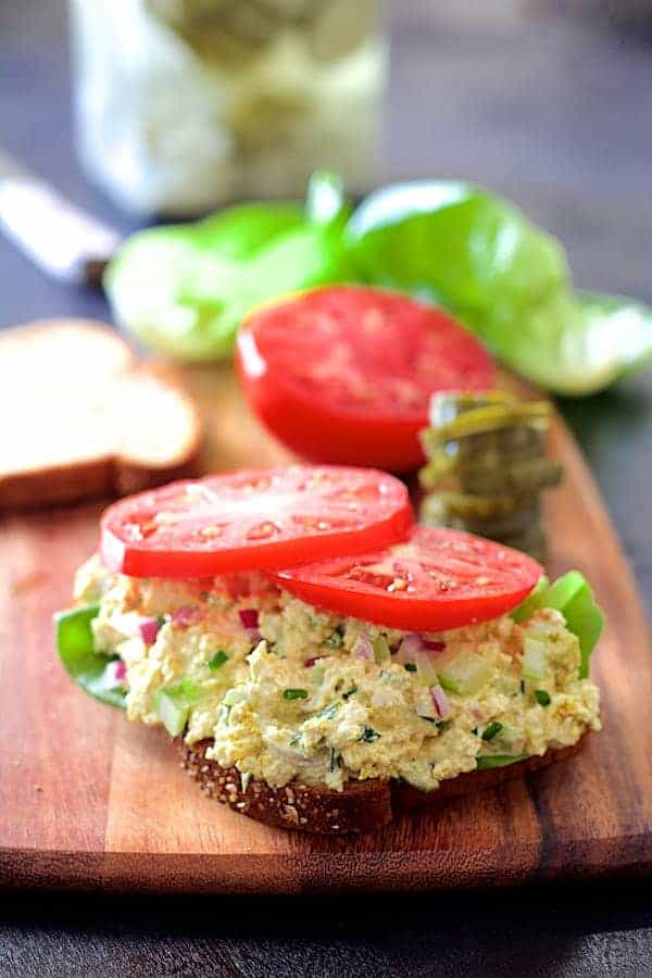 Curried Tofu Salad - Straight-on hero shot of salad on whole-grain bread on wood cutting board with fresh lettuce and tomato