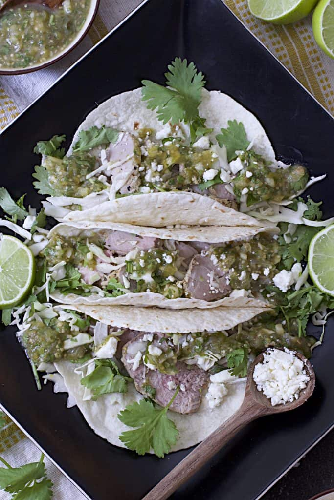 Close-up photo of Cumin Lime Roast Pork Tacos with Salsa Verde on black square plate.