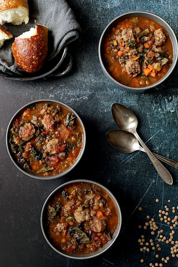 Photo of three bowls of Sausage and Lentil Soup with Kale with spoons and basket of bread.