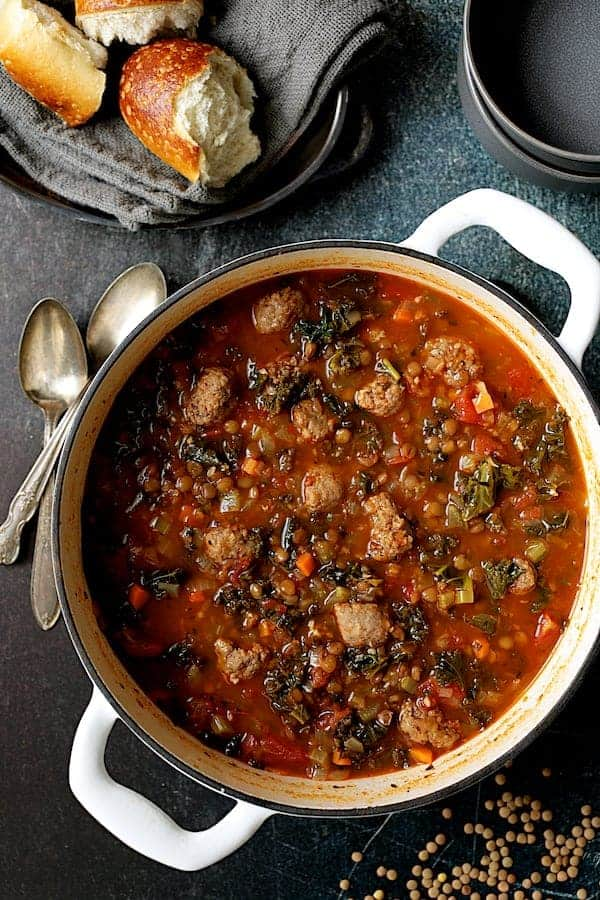 Sausage and Lentil Soup with Kale - Overhead shot of soup in white Dutch oven on teal background