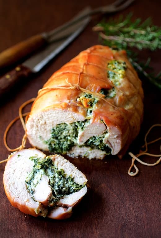 Spinach and Ricotta Stuffed Turkey Breast with Garlic and Herb Sauce - Straight-on close-up shot of turkey breast with one slice cut