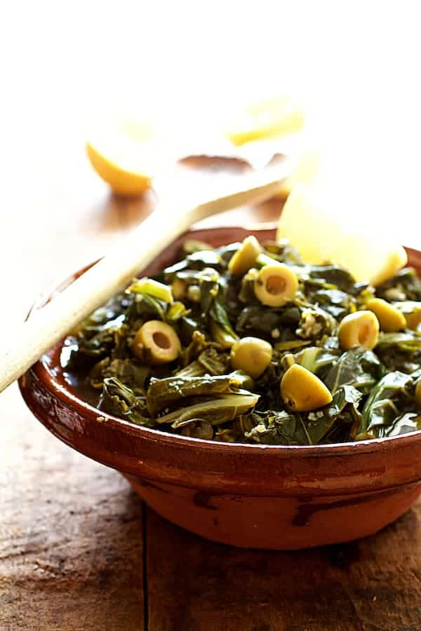 Braised Greens with Olives and Lemon - Straight-on shot of greens in clay bowl with serving spoon on the side