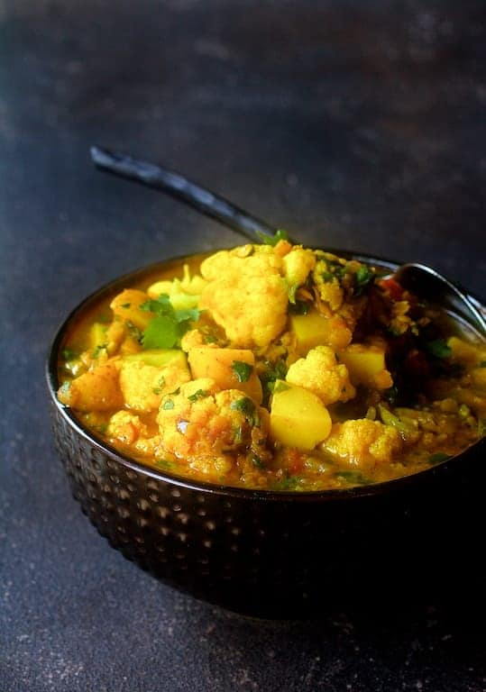 Cauliflower Red Lentil and Potato Curry - Hero shot of curry in decorative bowl with serving spoon
