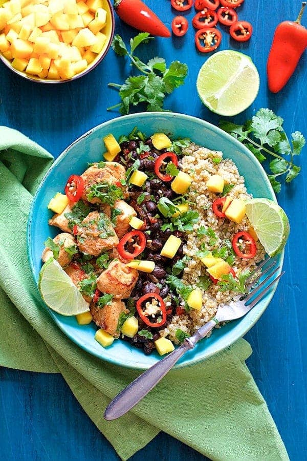 Photo of Cuban Chicken and Black Bean Quinoa Bowls in bright blue bowl on blue background on green napkin garnished with mango, lime, cilantro and red chiles.