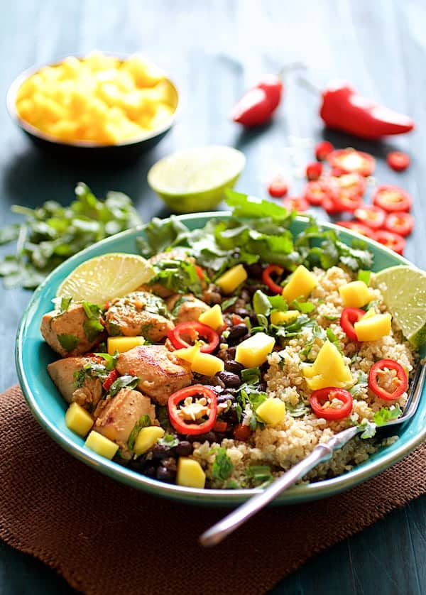 Photo of Cuban Chicken and Black Bean Quinoa Bowls on blue background garnished with mango, lime wedges, cilantro and Fresno chile.
