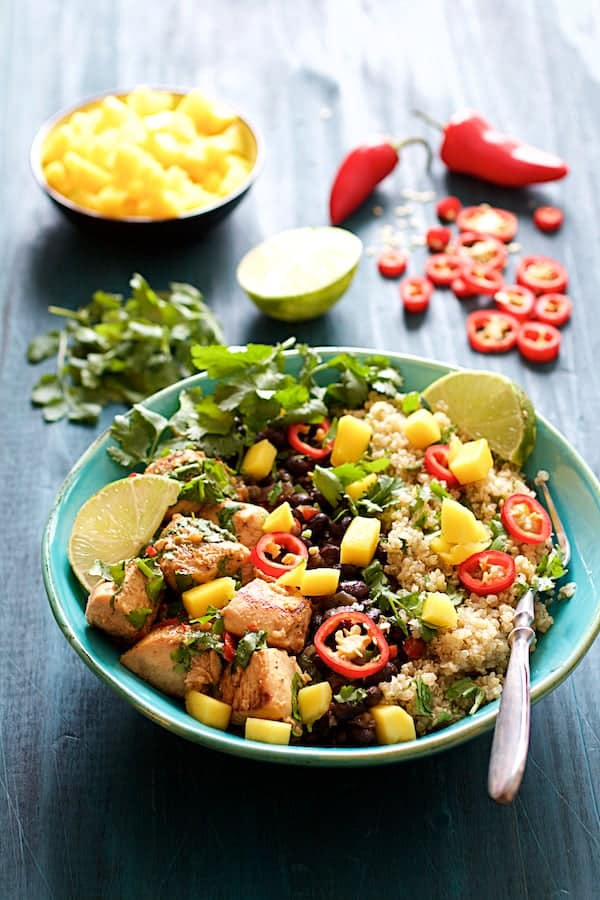 Photo of Cuban Chicken and Black Bean Quinoa Bowls with garnishes in the background.