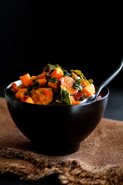 Chorizo Kale and Sweet Potato Stew - Close-up shot of stew on brown burlap with black background
