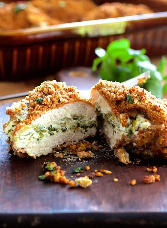Photo of one Green Chile Goat Cheese Stuffed Chicken Breasts with Spicy Pecan Cornmeal Crust cut in half on wood cutting board.