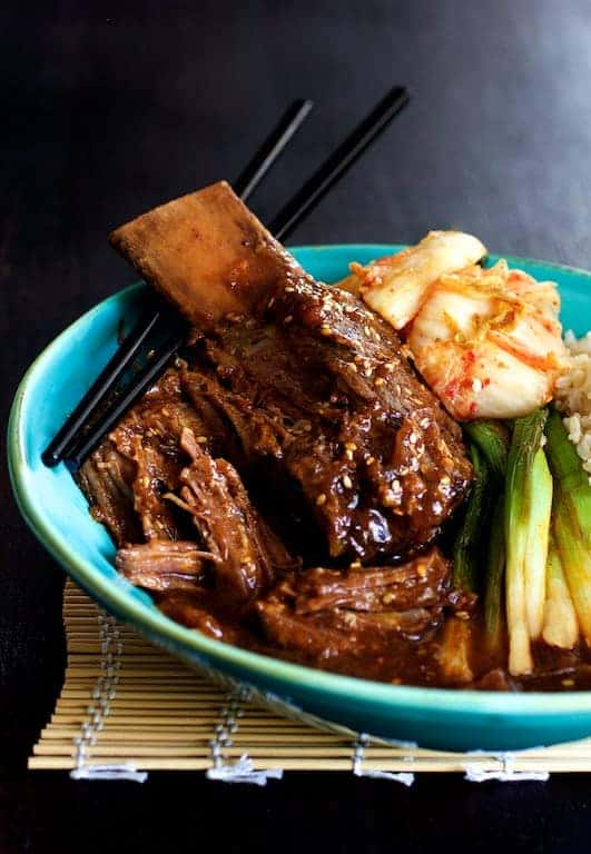 Korean Braised Beef Short Ribs - Hero close-up shot of short ribs in blue bowl with chopsticks, kimchi and scallions