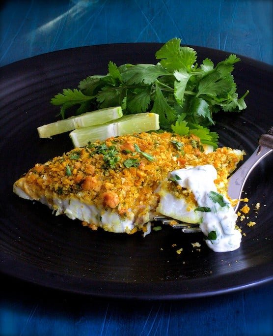 Photo of Curried Chickpea Encrusted Fish with Jalapeno - Lime Tartar Sauce on black plate garnished with cilantro and lime wedges.
