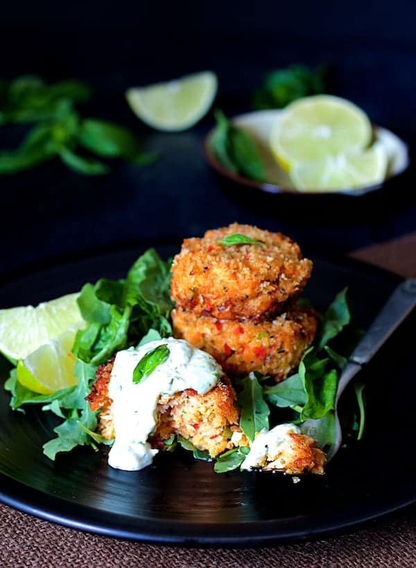 Photo of Thai Salmon Cakes with Basil - Lime Mayonnaise on black plate garnished with lime wedges and arugula.