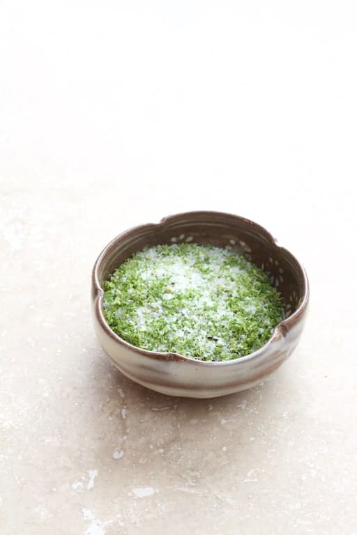 Lime Salt in small clay bowl on marble background
