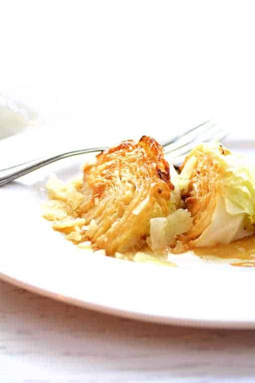 Parmesan Roasted Cabbage Wedges - Side view of cabbage wedges on white platter with serving fork in the background