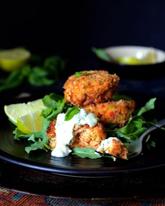 Photo of Thai Salmon Cakes with Basil - Lime Mayonnaise with some of the salmon cake on a fork garnished with lime wedges.