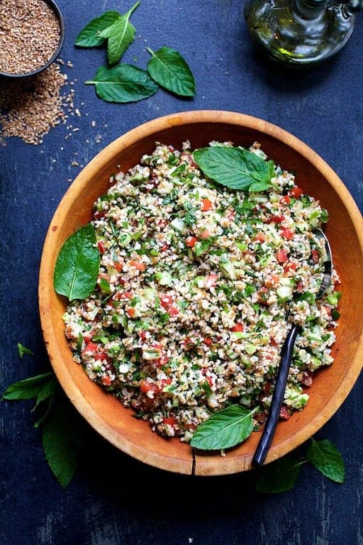 Photo of Tabouli with Fresh Jalapeno in wood bowl garnished with fresh mint leaves.