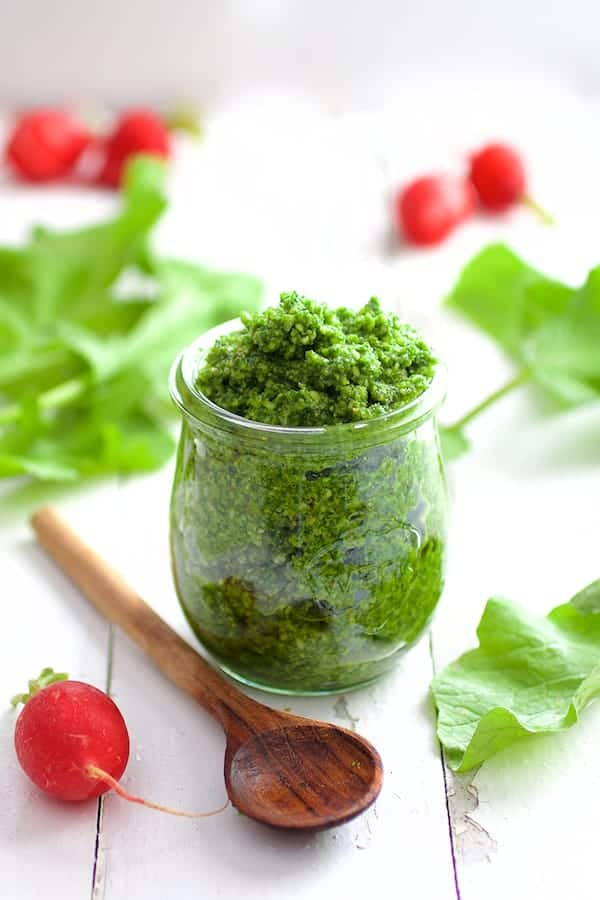 Radish Greens Pesto on white boards with wooden spoon