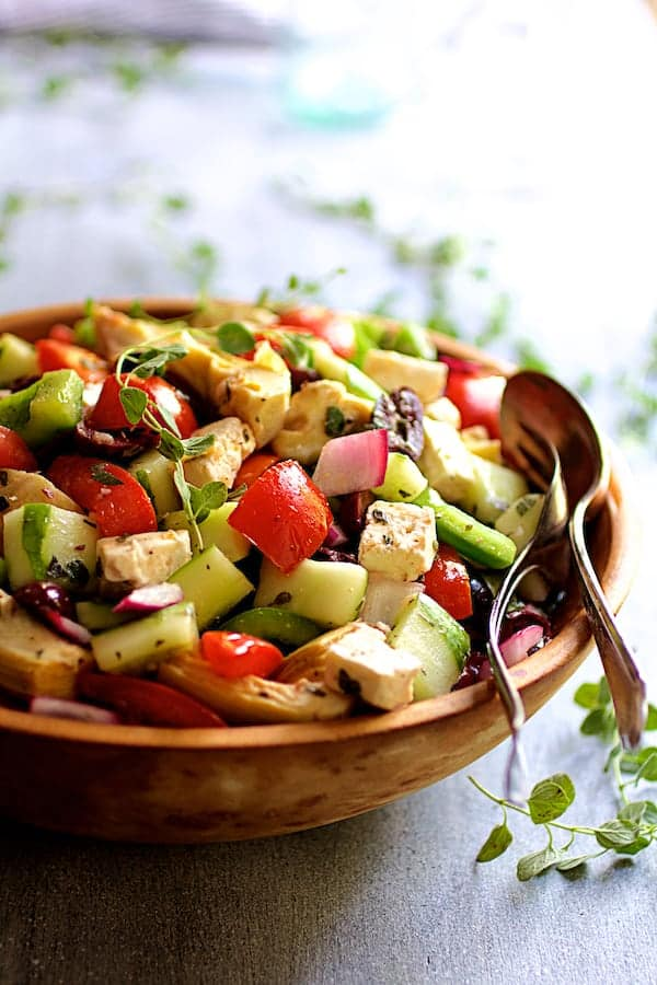 Greek Vegetable Salad with Marinated Feta Cheese - Hero shot in wood bowl with serving spoon and fork garnished with fresh oregano