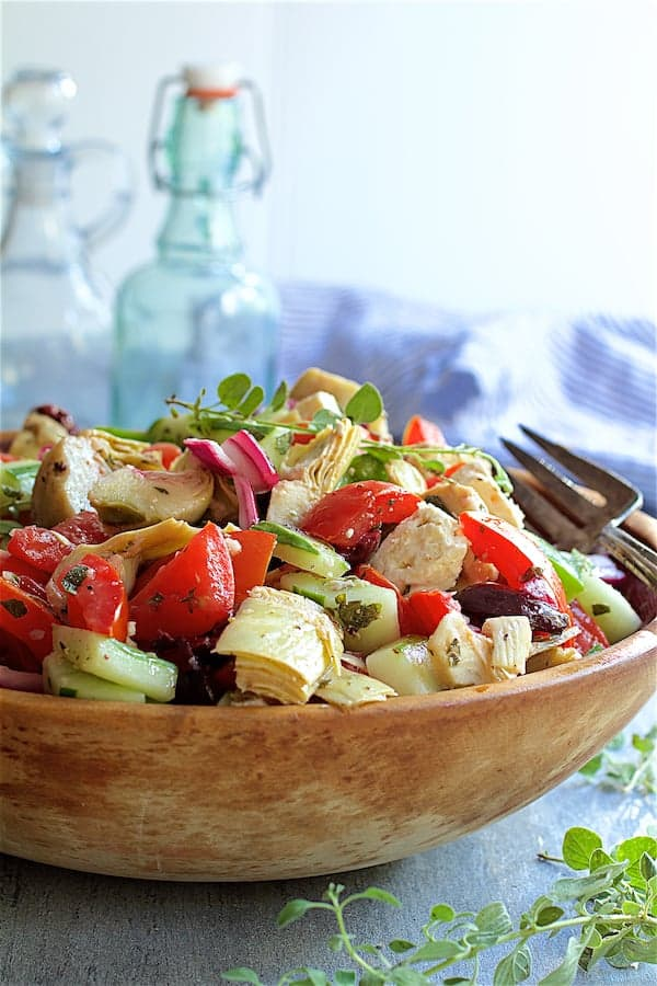 Greek Vegetable Salad with Marinated Feta Cheese - In wood bowl garnished with fresh oregano with bottles in the background and striped towel