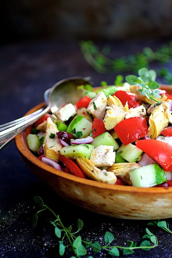 Greek Vegetable Salad with Marinated Feta Cheese - In wood bowl on dark blue background