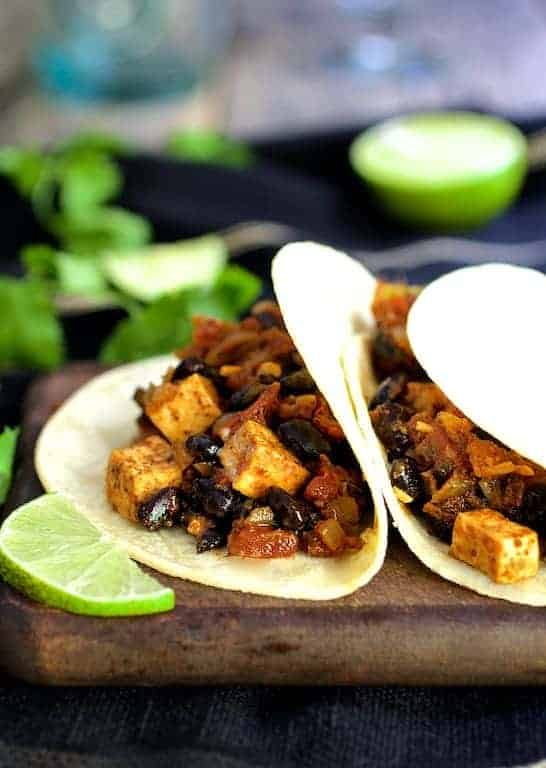 Tofu and Black Bean Tacos - Side view of tacos on wooden board garnished with lime wedges
