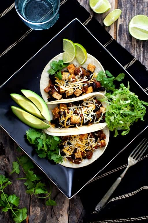 Tofu and Black Bean Tacos - Overhead shot of tacos on black square plate garnished with avocado, cilantro, lime wedges and lettuce