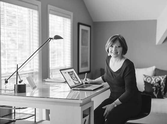 Photo of Carol Borchardt sitting at her desk in front of a computer.